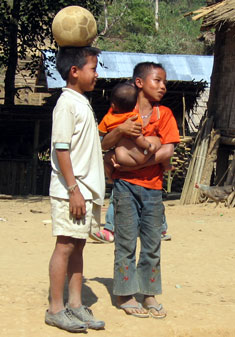 In Laos, a boy carries his little brother while his friend balances a ball.