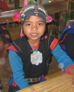 A young student in a remote Laotian village wears traditonal clothing.