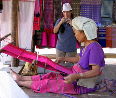 A village lady in Thailand, weaves cloth while a tourist takes a photo.
