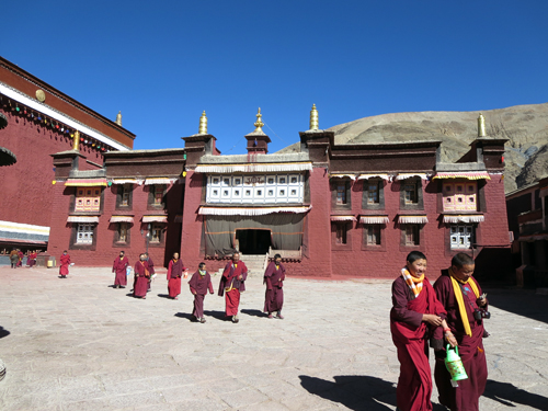 Buddhist monks walk the courtyard of Jokhang Temple