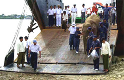 A white elephant is unloaded