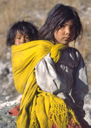 A young Tarahumara girl carries her little sister, in Mexicos Copper Canyon.