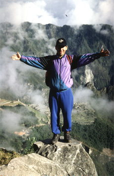 A Peruvian guide stands on a rock overlooking Machu Picchu.